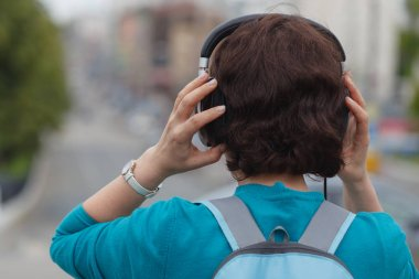 Beautiful brunette woman listening music with headphones in the city