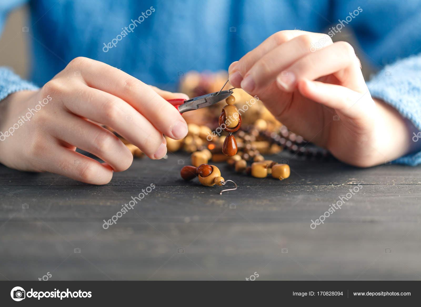 Person, die Herstellung von Schmuck mit Draht, Ketten und Perlen ...