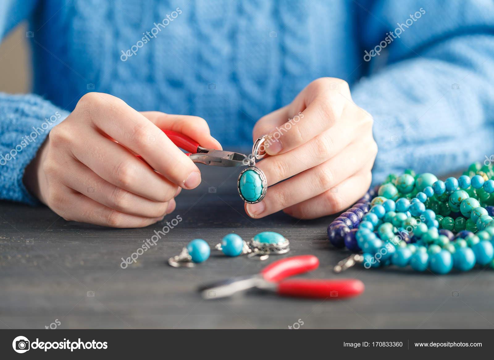Person, die Herstellung von Schmuck mit Draht, Ketten und Perlen und ...