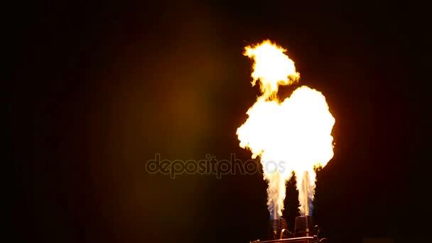 Plameny chrlí z přelomu dvou plynových hořáků na tmavém pozadí