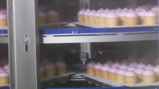 Zmrzlina v obchodě na továrny na zmrzlinu. Dopravníkové linky zmrzliny. Růžová ovocná vanilková zmrzlina v šálku vafle. Ice cream factory