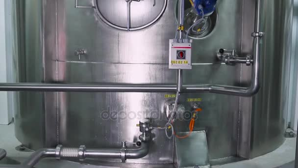 Chladicí systém v interiéru moderní továrny. Lesklé ocelové kovové trubky a modré motoru a ventily. Lesklý nerez trubky, nádrže pro potravinářský průmysl. Moderní zařízení na továrny na zmrzlinu