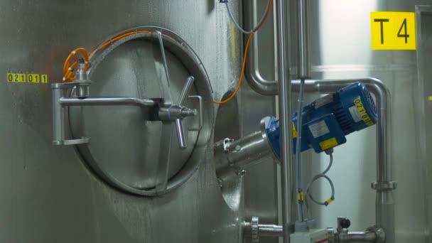Lesklé ocelové kovové trubky a modré motoru a ventily. Ocelové nádrže v interiéru moderní továrny. Potrubí ocel, moderní, lesklá je pokryta kapičky kondenzátu