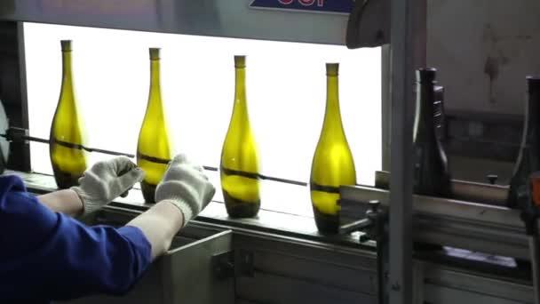 Pracovník kontroly kvality a čistoty skleněných lahví