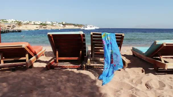 dřevěná židle na pláži pozadí modré moře a bílé jachty plováky