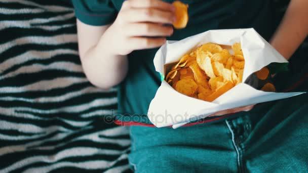 Chlapec dospívající jíst brambůrky s rukama na gauči doma