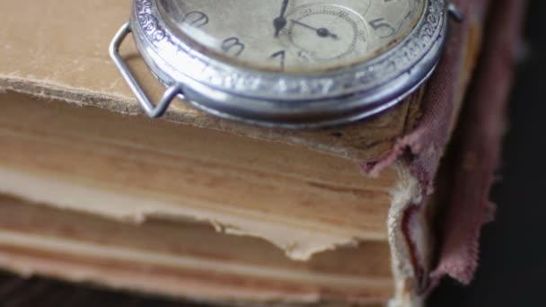 Vintage zsebóra mellett a régi fakó könyv,