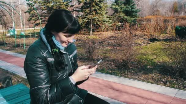 Das Mädchen gibt eine Meldung aus und führt einen Bildlauf durch die Seiten auf einem Smartphone in einem Frühlingspark