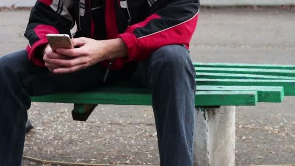 Osamělý muž sedí v parku na lavičce psát něco na smartphone