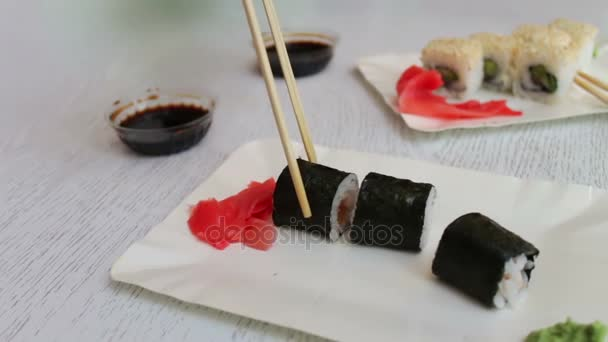 Köstliche Sushi-Maki mit Holzstäbchen nehmen und Tauchen Sie ein in Sojasauce, japanische Küche
