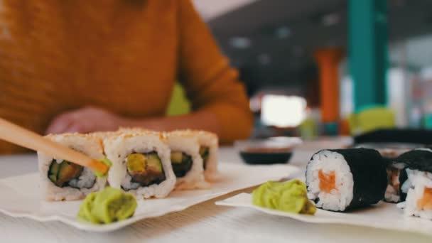 Dívka sedí bere s dřevěné tyče jsou zelené wasabi v kavárně na stůl sushi, japonská kuchyně