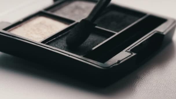 Gray shades of eyeshadow,Close up of makeup brush moving over eye shadows