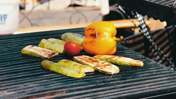 Velký gril na kterém esteticky rozloženy opečené klobásky, sladká paprika, zelenina, kuřecí maso. Pouliční občerstvení, rychlé občerstvení, Snack na ulici, taseful, vynikající