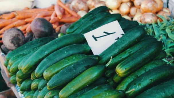 Ízletes friss uborka, paradicsom és egyéb zöldségek, árcédulák hazugságot piaci pult