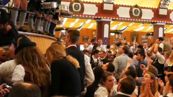 17. September 2017 - München, Deutschland: viele betrunkene Männer feiern und tanzen in einer Bierhalle. Die innen- und außen Aufnahmen in Lowenbreu Bierzelt.