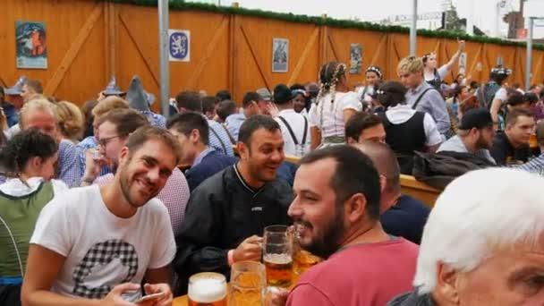 17. September 2017 - München, Deutschland: junge Menschen sitzen und feiern im Biergarten auf dem weltweiten bayerischen Festival Oktoberfest. Menschen trinken Bier aus großen Glas Gläser