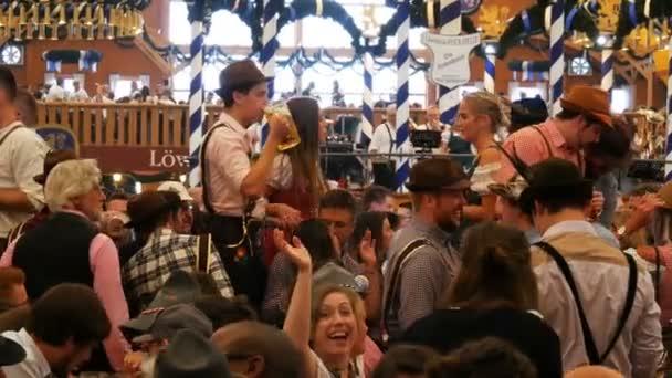 17. September 2017 - München, Deutschland: Weltberühmtes Oktoberfest, Menschen sitzen in Kneipen oder Bierzelten und trinken Bier mit Bäckern, lachen, haben Spaß und feiern