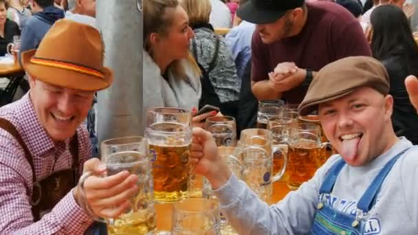 17. september 2017 - München, Deutschland: junge fröhliche Menschen ruhen sich im Biergarten aus und trinken Bier aus großen Bechern auf dem Oktoberfest in Bayern