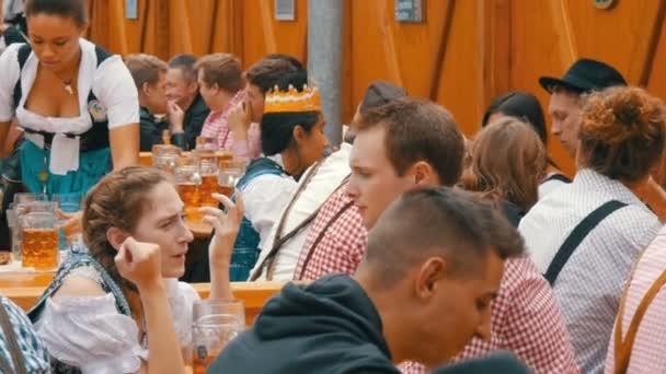 17. September 2017 - Oktoberfest, München: Menschen sitzen trinken Bier aus riesigen Glas Tassen auf Theresienwiese in Bayern auf dem Bierfest der Welt