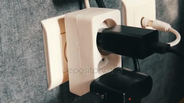 Sok dugók a fali konnektorból. Adaptert a töltőt a fali konnektorból