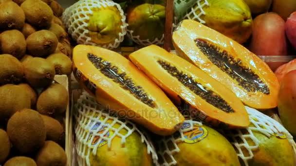 September 22, 2017 - Barcelona, Spain, Mercator de la Boqueria Food Market: a huge counter with tropical fruits, mangoes,papaya, kiwi, bananas in plastic packaging