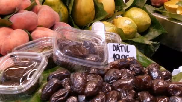 Various tropical fruits mango kiwi peaches dates on food market counter