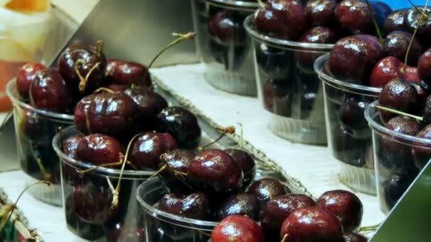 Various cherry tropical fruits mango kiwi peaches dates on food market counter