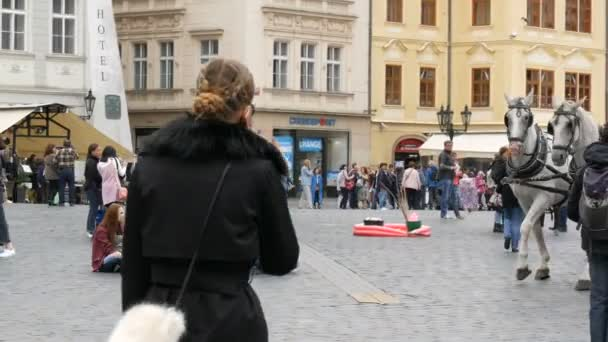 12. September 2017 - Prag, Tschechische Republik: Gesellschaft von Teenager-Mädchen sitzen in einem Kreis auf dem Asphalt, vorbei an der Hochzeit Wagenkolonne mit weißen Trainer und Pferden, die Braut und der Bräutigam sitzen im Inneren