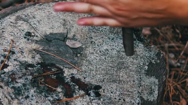 Ženy v lese otočí hůlkou v ruce, který otírá strom a snaží, aby oheň