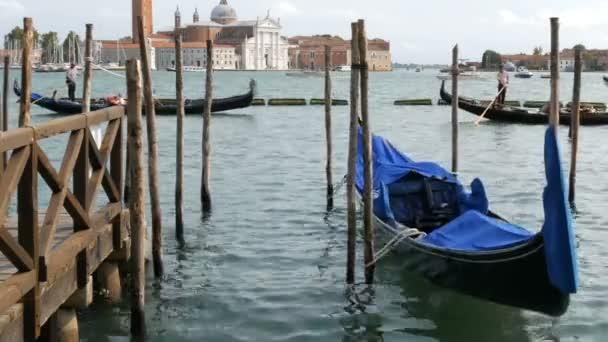 Gyönyörű fekete gondolák állvány és a rock, a hullámok a velencei Canal Grandéra