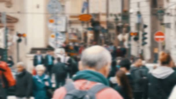 Busy anonymous people out of focus are walking.Crowd of people in a megapolis crosses the street and passes each other