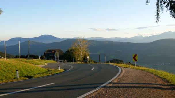 Krásná horská silnice v rakouských Alpách na které vyjížďky na motorce, pohled z hor a zelené louky