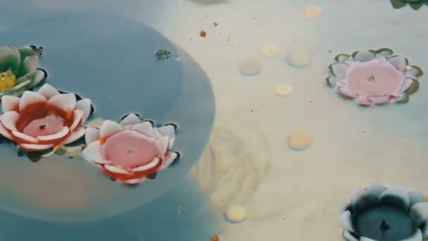 Krásný vosk barevné svíčky v podobě lotosových květů spalování a zaniklé plovoucí na vodě, detailní zobrazení