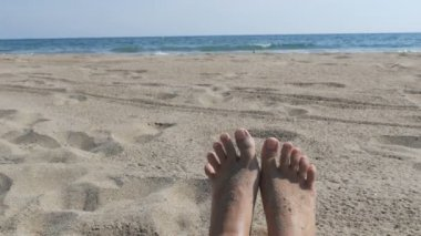 Female feet sunbathing on beach against the background of sand and blue sea with waves. Womans bare feet on a beach