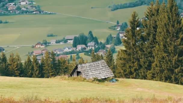 Hangulatos nagyon régi vintage fából készült ház az osztrák Alpokban, egy dombon, a zöld fű a háttérben az új, modern házak, régi, vidéki ország faház faluban