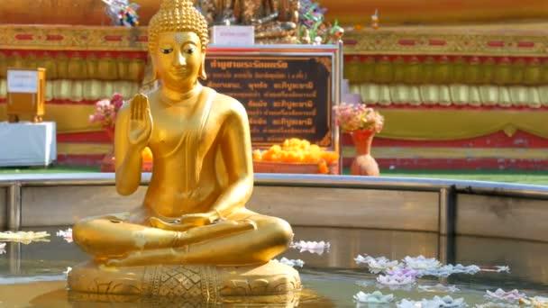 Pattaya, Thajsko - 18 prosince 2017: Zlatá socha sedícího Buddhu v malém rybníku nad které plovoucí svíčky vosk v různých barvách