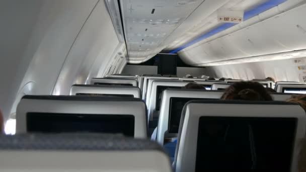 Cestující v pohodlných sedadlech letadel s mapami na obrazovkách v křeslech