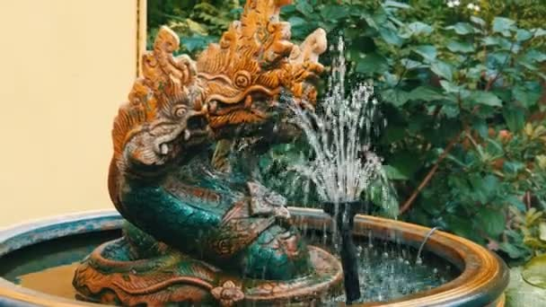 Three-headed green dragon as a traditional Buddhist symbol. Statue and a fountain of dragon in the garden of Thailand