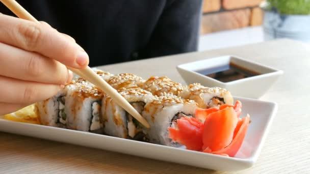 Ein Teenager nimmt Sushi-Rolle mit chinesischen Bambusstäben und lässt sie in Sojasauce fallen, nimmt ein Stück rosa Ingwer. Japanische Küche auf weißem Porzellanteller neben grünem Wasabi-Ingwer und Sauce