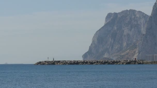 Mediterranean Sea in its beautiful waves, beating against white sand and the Rock of Gibraltar against background