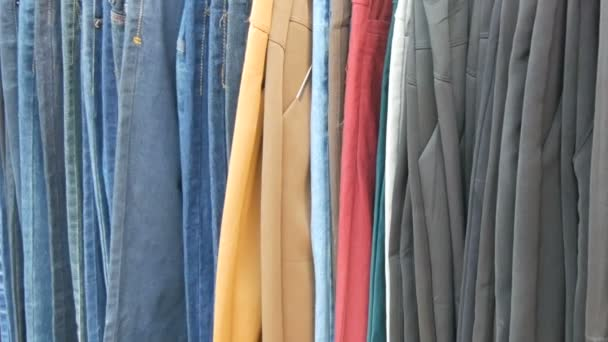 Pants hang on hanger, women look at clothes and choose. Flea market, clothes sold on the market