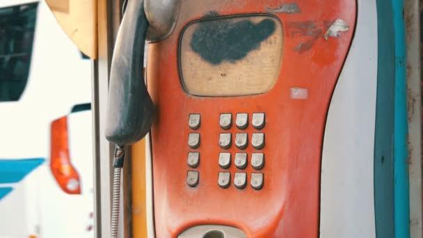 Staré ošuntělé červené telefon na město ulice. Retro telefon v telefonní budce