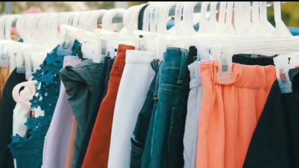 Things hang on hanger, women look at clothes and choose. Flea market, clothes sold on the market