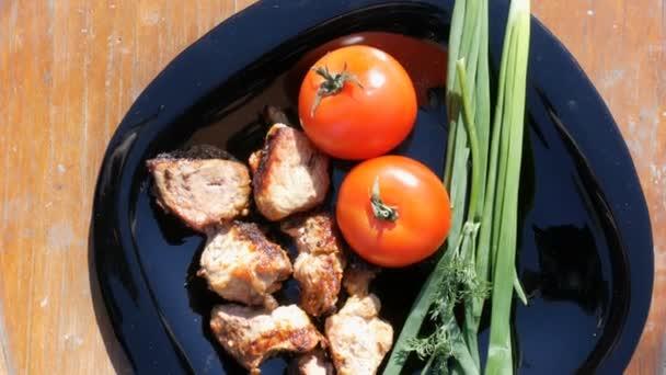 Krásně zdobené misky s kousky smažených steak, rajčat a zelených. Grilování masa nebo ražniči na černé nádobí