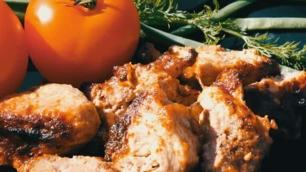 schön dekorierte Gericht mit Steakstücken auf dem Feuer gebraten, Tomaten und Gemüse. Fleischgrill oder ein Dönerspieß auf schwarzem Teller in der Natur