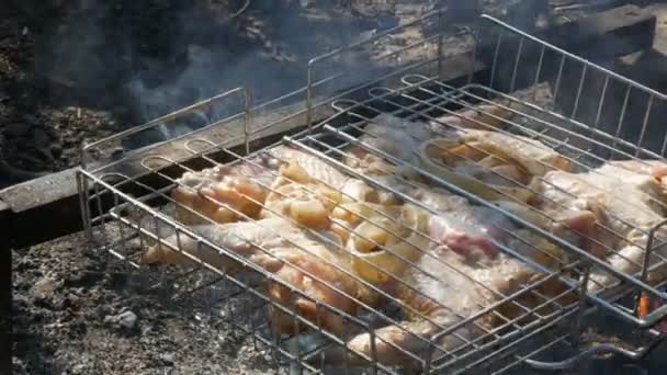 Chicken wings marinated in mayonnaise, seasonings and in onions grilled on fire. Hand overturns the grate