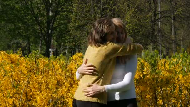 An adult daughter runs up and meets an elderly adult mother hugging her and kissing her. Spring Mothers Day