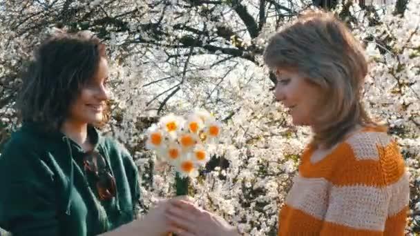 Porträt einer erwachsenen Mutter mittleren Alters und ihrer erwachsenen Tochter, die vor dem Hintergrund eines blühenden Baumes einen Strauß Narzissen zum Muttertag schenkt