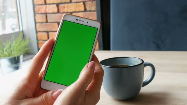 Zelená obrazovka smartphone. Chroma klíč na bílý smartphone, ženské ruce držet mobilní telefon v kavárně u šálku kávy