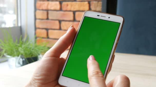 Zelená obrazovka smartphone. Chroma klíč na bílý smartphone, ženské ruce držet mobilní telefon v kavárně